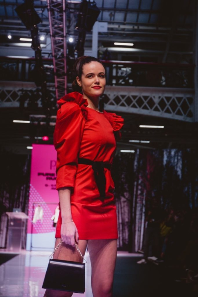 SEO Alt Text: Model Amanda Sarco Styled By Roberta Lee, Pure London Runway Feb 2020 | Conscious Fashion Brands | Red Dress, Black Clutch Bag