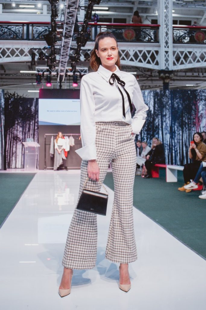 SEO Alt Text: Model Amanda Sarco Styled By Roberta Lee, Pure London Runway Feb 2020 | Conscious Fashion Brands | White T-Shirt, Check Trousers, Black Bag