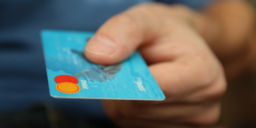 Holding a credit card | What is Cost per Wear? | Wardrobe Investments | Sustainable Closet Tips
